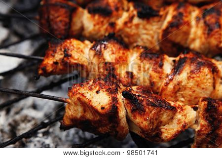 fresh hot grilled chicken shish kebab barbecue on grid over charcoal