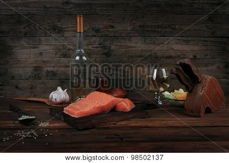 fresh raw salmon fillet served with lemon and white wine in wineglass, bottle, on dark plate over vintage wood table with handmade cutlery knife and spice on spoon with empty space background