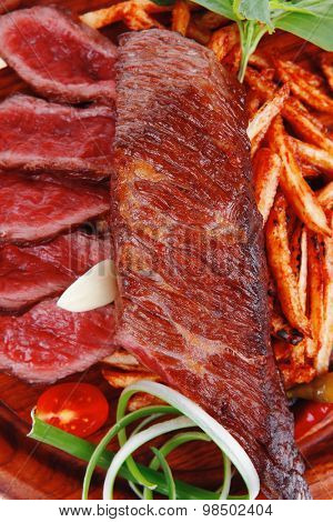 meat food : grill beef on potato chips with fresh tomato and hot green peppers on wood plate isolated on white background