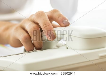 Closeup Of Female Secretary Holding Telephone Receiver Of White Landline Phone