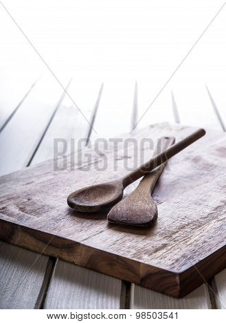 Wooden kitchen utensils on the board. Wooden spoon on the wooden board and table.