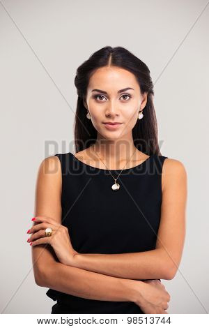 Jewerly concept. Portrait of a cute female model in black dress posing isolated on a white background. Looking at camera