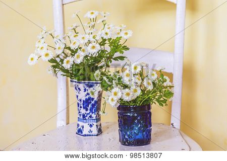 Feverfew in vases with an vintagae look.