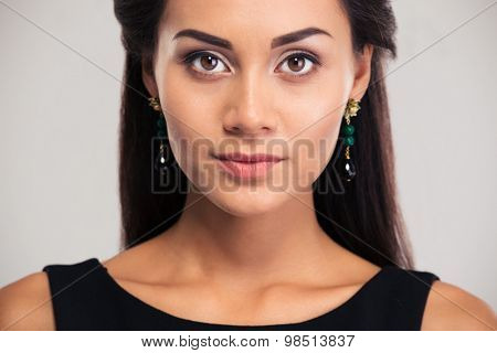 Jewelry concept. Portrait of a charming female girl with fresh skin looking at camera isolated on a white background