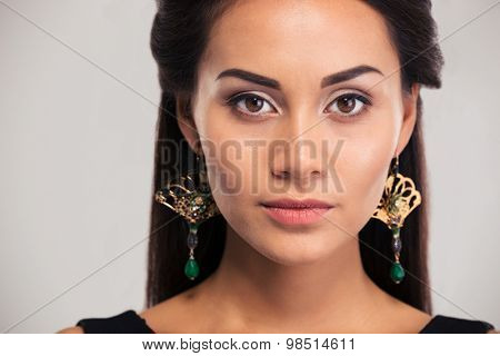 Jewelry concept. Charming young woman looking at camera isolated on a white background