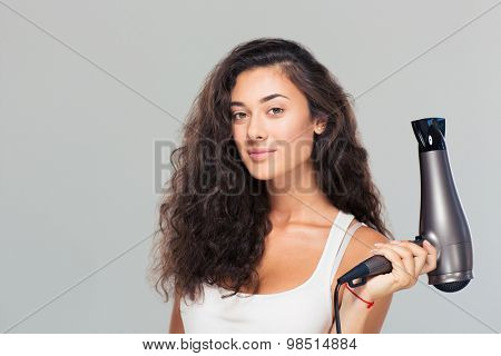 Cute attractive woman holding hairdryer over gray background. Looking at camera