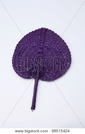 Purple color native fan made from palm leaves on white background