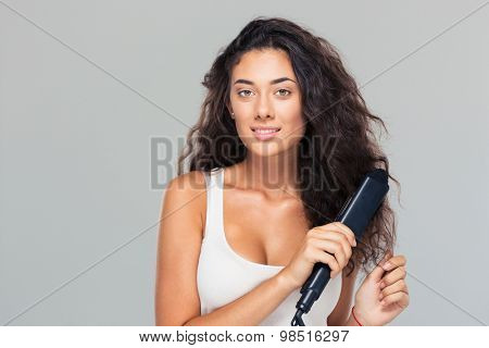 Happy young woman doing hairstyle with hair straightener over gray background