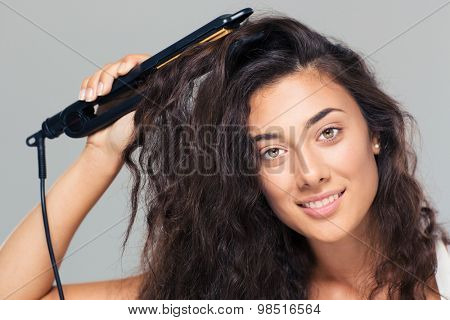 Portrait of a smiling pretty woman doing hairstyle with hair straightener over gray background. Looking at camera