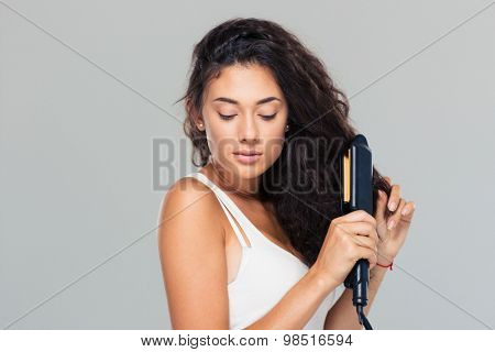 Portrait of a cute woman doing hairstyle with hair straightener over gray background