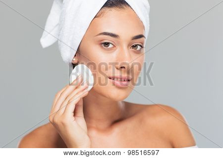 Spa concept. Portrait of a cute woman with wadded disk over gray background. Looking at camera