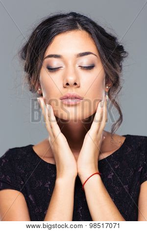 Beauty portrait of a charming woman with closed eyes on gray background