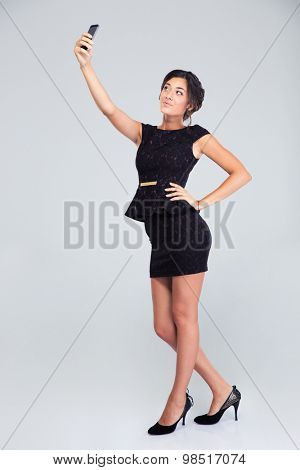 Full length portrait of a cute woman in black dress making selfie photo on smartphone isolated on a white background