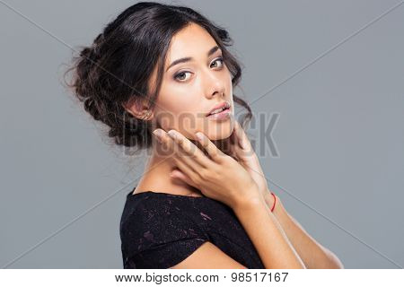 Beauty portrait of attractive woman posing on gray background. Looking at camera