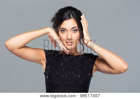 Beauty portrait of a pretty woman standing over gray background and looking at camera