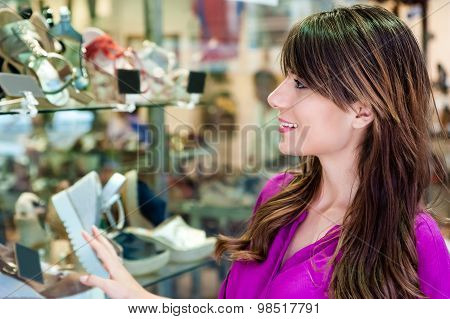 Young woman in front a shoes shop window looking at the shoes and smiling.