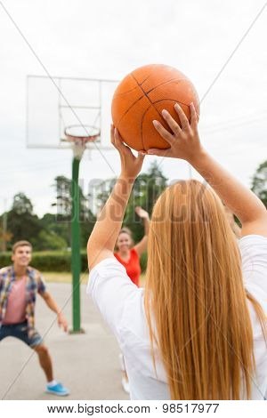 summer vacation, sport, games and friendship concept - group of happy teenagers playing basketball outdoors from back