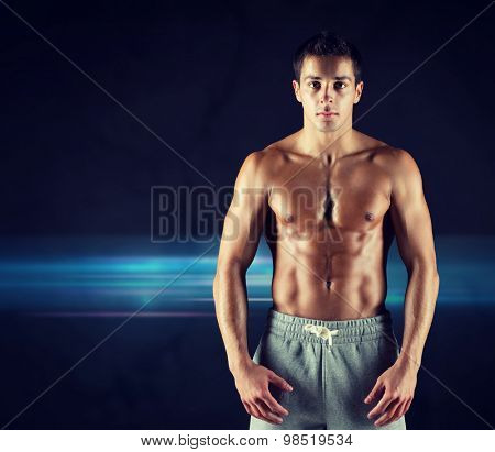 sport, bodybuilding, strength and people concept - young man with bare muscular torso standing over dark background