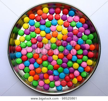Colorful bonbons kept on a plate on a plain background