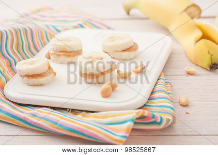 banana slices with peanut butter on white board