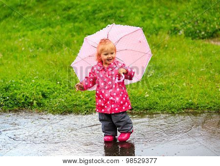 cute little girl having fun on rain