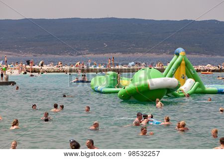 SELCE, CROATIA - JULY 24, 2015: People swimming and children playing on inflated saturn baloon on the Selce beach