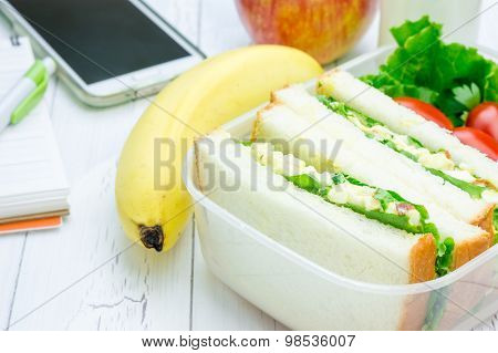 Lunch Box With Egg Salad Sandwiches, Fruits, Milk And Stationery