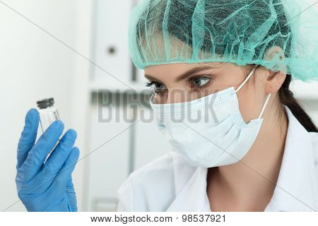 Medical Doctor Looking At Small Flask With Liquid