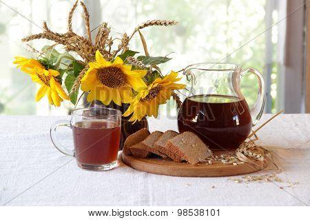Kvass (kvas) In A Transparent Jug And A Bouquet Of Sunflowers