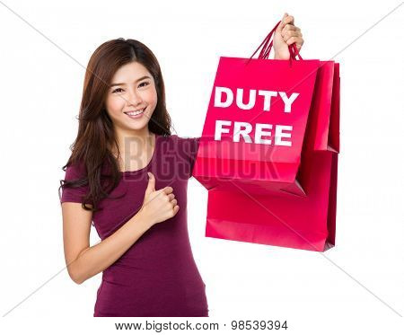 Happy shopping young woman with thumb up gesture and holding bag showing duty free