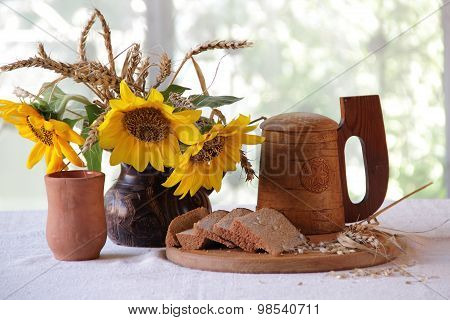 Kvass (kvas) In A Clay Cup, A Wooden Mug And A Bouquet Of Sunflowers