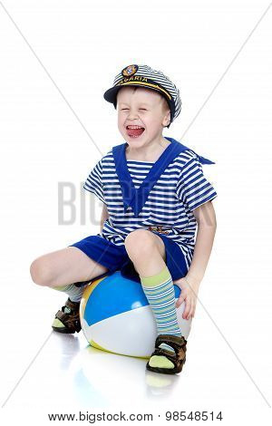 The boy sits on the ball
