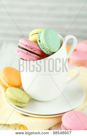 French Colorful Macarons In Cup On White Wooden Background