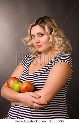 Portrait of beautiful young pregnant woman of blonde. She sits on a chair and holds red and green ap