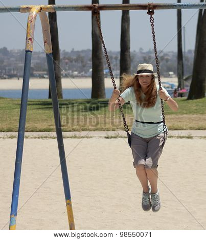 A Woman Swings In A Park By A Bay