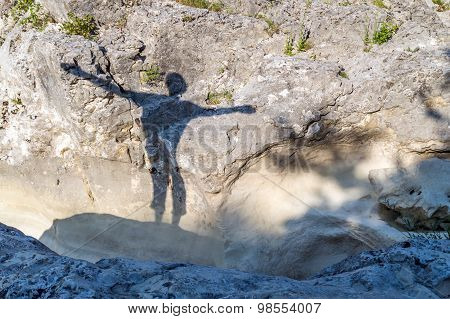 Silhouette Of A Happy Person Outdoor On The Rocks, With Arms wide Spread
