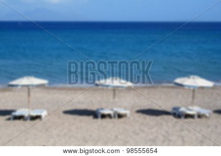 Greece. Kos. Kefalos Beach. Chairs And Umbrellas On The Beach. In Blur Style