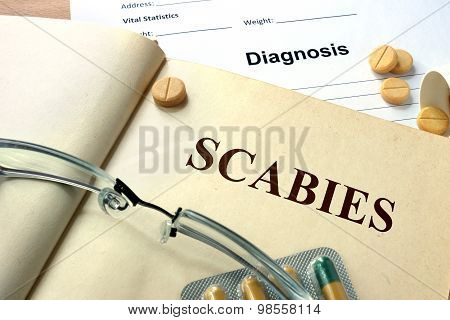 Word Scabies  on a paper and pills.