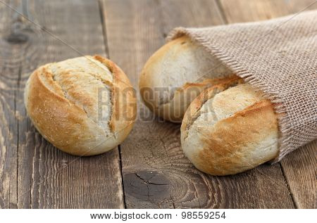 Bread roll in burlap sack on wooden table