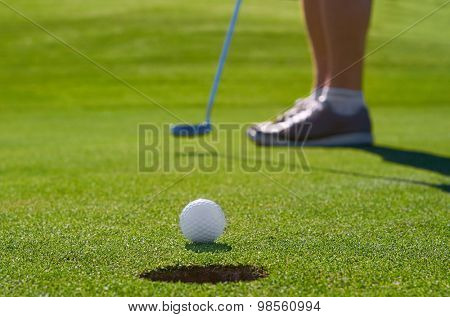 golfer putting ball into hole