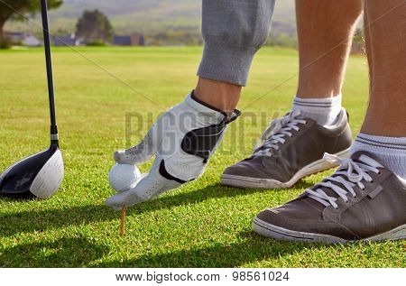 golf man placing ball for tee shot on vacation