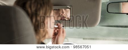 Woman Puting The Lipstick On