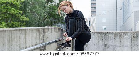 Woman Tying Shoelaces During Run
