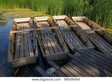 summer scene - four wooden boats on a lake