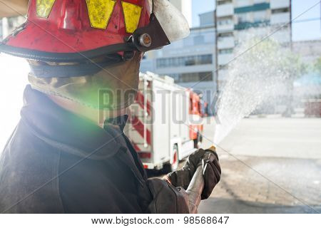 Side view of male firefighter spraying water while practicing at fire station