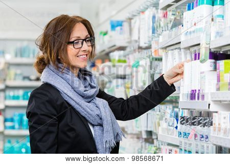 Smiling female consumer choosing product in pharmacy