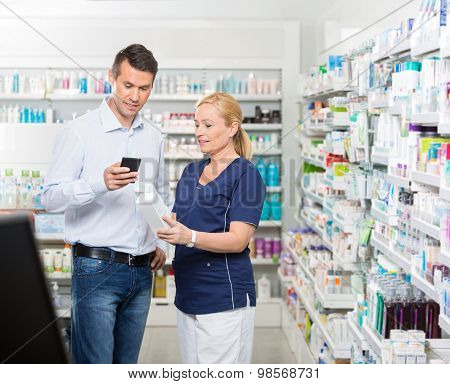 Male customer using mobile phone while chemist holding products in pharmacy