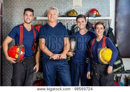 Portrait of confident firefighters standing together at fire station