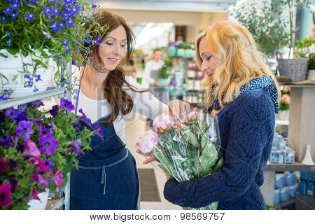 Florist guiding female customer in buying flowers at store