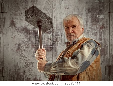 Angry old worker man holding a hammer